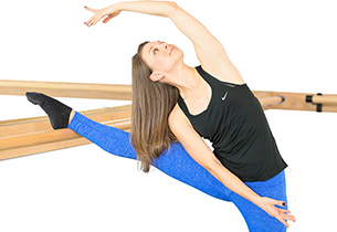 Stacey Our Barre Instructor doing a graceful exercise pose while teaching a class at our Lincoln Park Chicago Studio